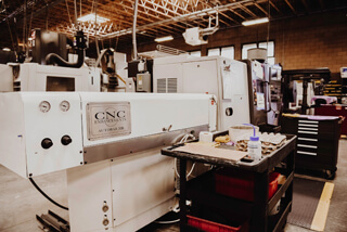 white CNC machine with black cart beside it inside of a machine shop